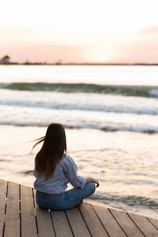 Rückansicht frau, die draußen meditiert