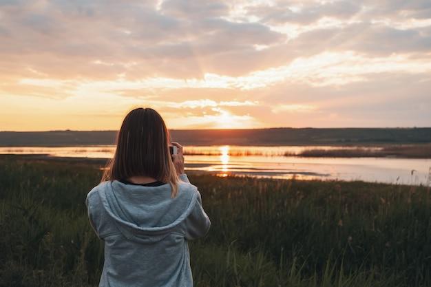 Rückansicht frau, die fotos mit einem smartphone am strand während sonnenuntergang oder sonnenaufgang macht