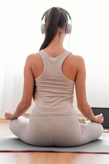 Rückansicht frau, die zu hause mit kopfhörern meditiert
