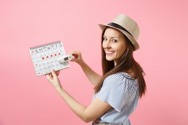 Rückansicht frau im kleid hält in der hand thermometer, kalender der weiblichen perioden, überprüfung der menstruationstage einzeln auf rosafarbenem hintergrund. medizinisches gesundheitswesen, gynäkologisches konzept des eisprungs. platz kopieren