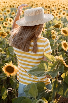Rückansicht frau im sonnenblumenfeld