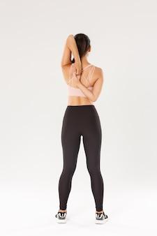 Rückansicht in voller länge des aktiven und schlanken brünetten asiatischen fitnessmädchens, aufwärmen der sportlerin vor yoga-klassen, sperren der hände hinter dem rücken, sportlerin, die dehnübungen macht, weißer hintergrund.