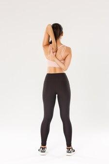 Rückansicht in voller länge des aktiven und schlanken brünetten asiatischen fitnessmädchens, aufwärmerin der sportlerin vor yoga-klassen, hände hinter dem rücken sperren, sportlerin, die dehnübungen macht, weißer hintergrund.