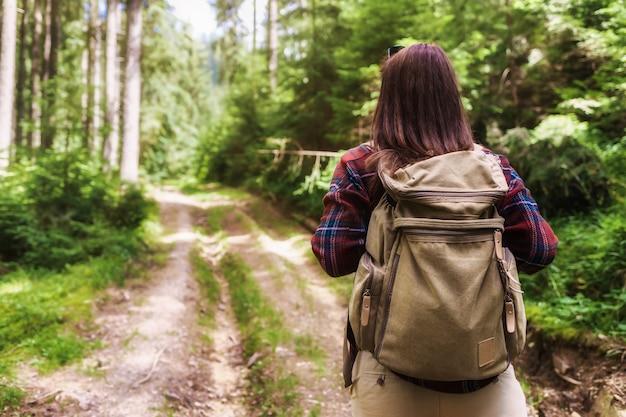 Rückansicht junge frau tourist geht mit backpacker im wald