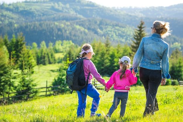 Rückansicht junge mutter und zwei töchter gehen den mit grünem gras bewachsenen hügel hinunter. herrlicher blick auf den wald, der während des trekkings an einem warmen sommertag auf den bergen wächst