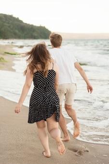 Rückansicht junge und mädchen, die zusammen am strand spazieren gehen