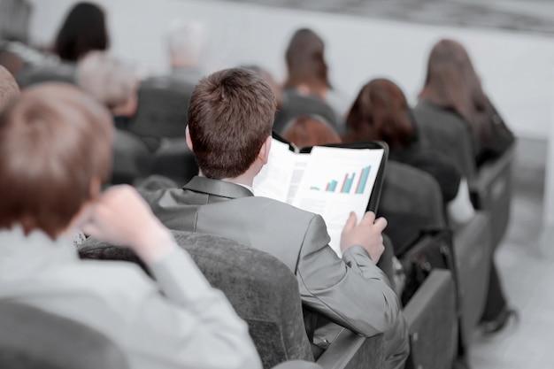 Rückansicht. junge unternehmer hören dem redner auf der geschäftskonferenz zu. wirtschaft und bildung
