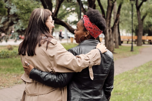 Rückansicht junger fröhlicher frauen, die beim spaziergang im park interagieren