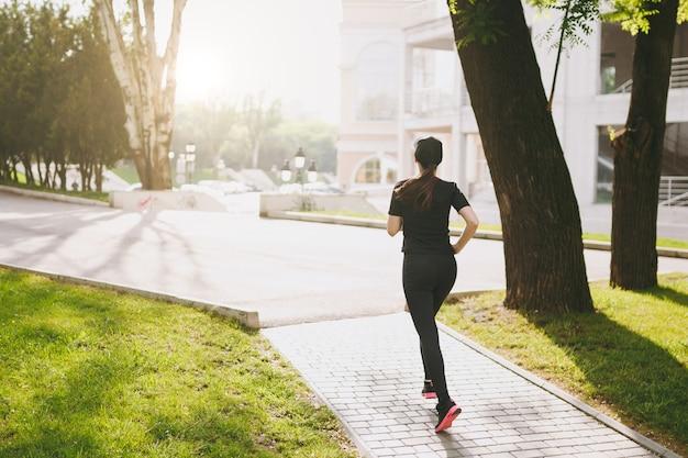Rückansicht junges athletisches brünettes mädchen in schwarzer uniform und mützentraining, sportübungen und laufen, direkt auf den weg im stadtpark im freien schauend
