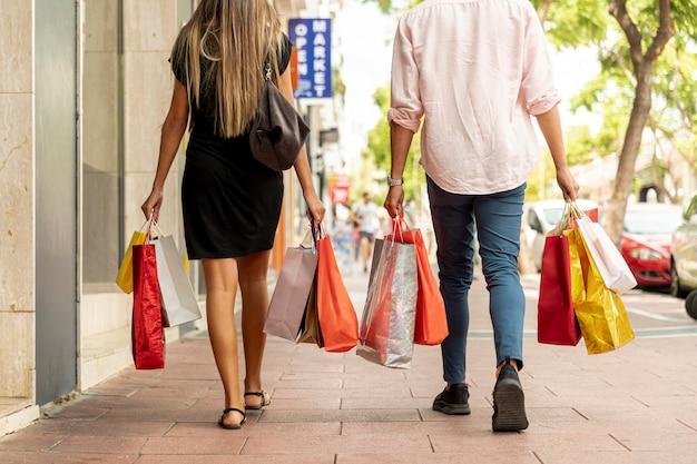 Rückansicht junges paar mit taschen spazieren