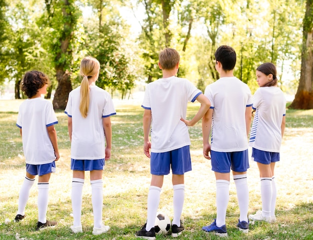 Rückansicht kinder, die bereit sind, ein fußballspiel zu spielen