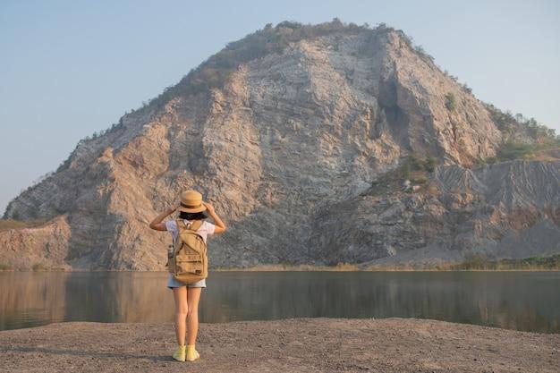 Rückansicht kleines asiatisches mädchen, das die schöne aussicht auf die felsigen berge und den see bewundert