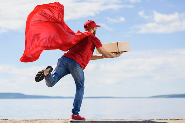Rückansicht-lieferbote, der superheldenumhang trägt