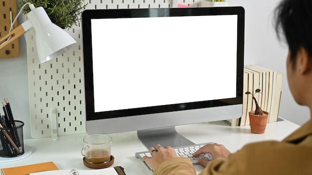 Rückansicht männlich, der mit computer zu hause arbeitet.