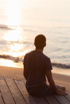 Rückansicht mann, der am strand meditiert