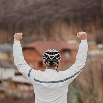 Rückansicht mann mit fahrradsicherheitshut auf seinem kopf