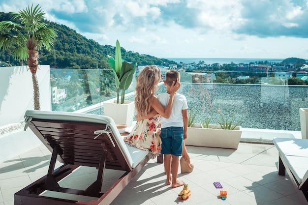 Rückansicht: mutter und sohn betrachten die aussicht vom balkon ihres hotels.