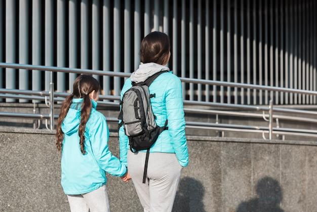 Rückansicht mutter und tochter, die einen spaziergang machen