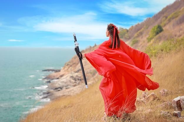 Rückansicht porträt der jungen und schönen frau, die rotes chinesisches kriegerkostüm mit schwarzem schwert trägt, sie postiert unter verwendung des schwertes auf berg mit meer und natur im freien