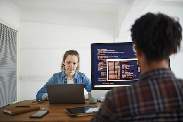 Rückansicht porträt des afroamerikanischen mannes, der code auf computerbildschirm schreibt, während am schreibtisch in der softwareentwicklungsagentur mit kollegin unter verwendung des laptops im hintergrund, kopienraum arbeitet