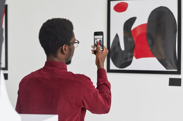 Rückansicht porträt des jungen afroamerikanischen mannes, der foto der malerei über smartphone bei der ausstellung der zeitgenössischen kunstgalerie macht,