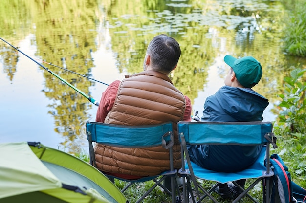 Rückansicht porträt des liebenden vaters und des sohnes, die zusammen während des campingausfluges durch see fischen, kopieren raum