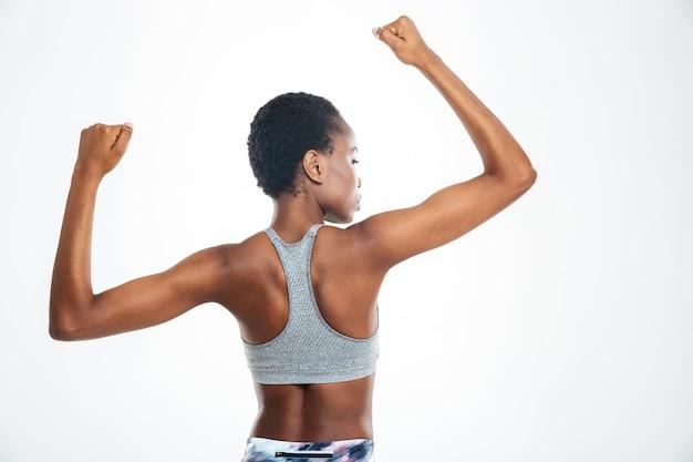 Rückansicht porträt einer afroamerikanischen frau, die ihren bizeps isoliert auf einem hintergrund zeigt