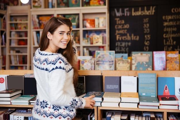 Rückansicht porträt einer hübschen jungen frau, die bücher in der bibliothek auswählt