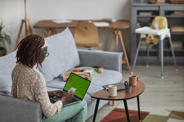 Rückansicht porträt einer jungen afroamerikanischen frau, die laptop mit grünem bildschirm verwendet und kreditkarte hält, während sie zu hause auf dem sofa sitzt, platz kopieren