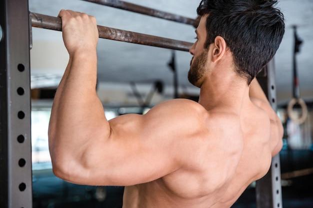Rückansicht-porträt eines amuskulären mannes, der sich im fitnessstudio an der reckstange festzieht