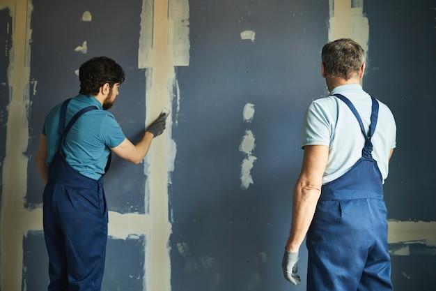 Rückansicht porträt von zwei bauarbeitern, die trockenmauer bauen, während haus renovieren, raum kopieren