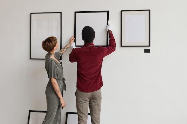 Rückansicht porträt von zwei kunstgaleriearbeitern, die malrahmen an weißer wand hängen, während ausstellung im museum planen,