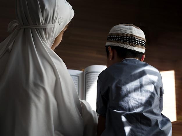 Rückansicht religiöser asiatischer muslimischer kinder lernen den koran und studieren den islam, nachdem sie zu hause zu gott gebetet haben. sonnenuntergangslicht scheint durch das fenster. friedliches und wunderbar warmes klima.