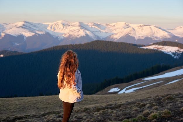 Rückansicht schoss von einer frau, die in den bergen wandert, die herum schauen