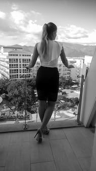 Rückansicht schwarz-weiß-foto der schönen geschäftsfrau in weißem hemd und schwarzem rock, die auf einem luxuriösen hotelbalkon posiert und auf stadt und berge schaut.