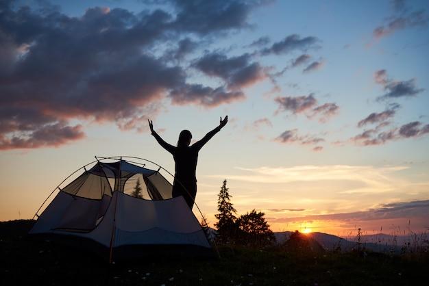 Rückansicht silhouette frau, die mit offenen armen nahe zelt oben auf berg mit wildblumen und tannenbäumen bei tagesanbruch steht. einzigartige landschaft des abendhimmels und des sonnenuntergangs hinter bergen und hügeln