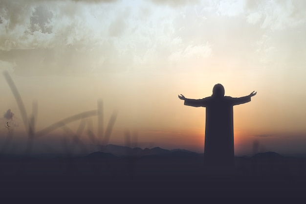 Rückansicht silhouette von jesus christus hob die hände und betete zu gott mit einem sonnenuntergang himmel