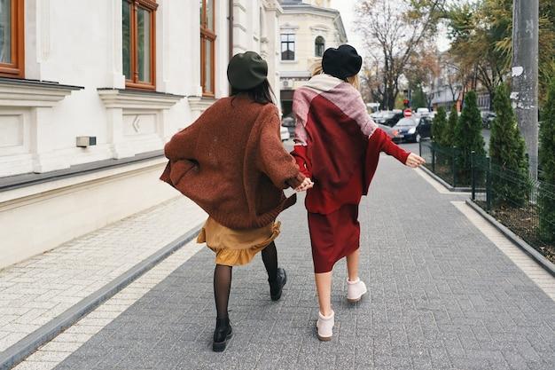 Rückansicht. sorglose modische damenmodelle in eleganter herbstkleidung und brille. junge mode-mädchen in stilvollen gewebten wollkleidern und hüten über stadtstadt, herbstporträt.
