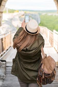 Rückansicht stilvoller reisender, der bilder im freien macht
