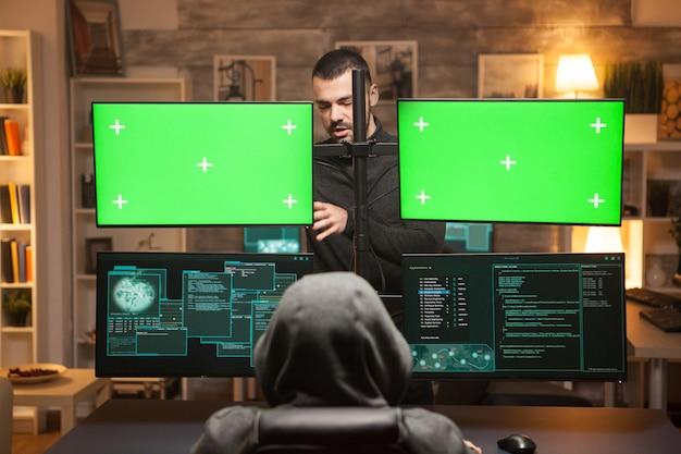 Rückansicht-team von hackern, die cyber-angriffe vor computer mit grünen bildschirmen durchführen.