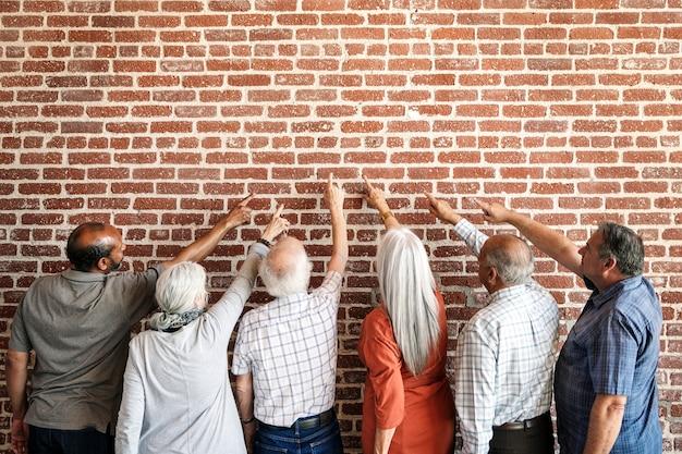 Rückansicht von älteren menschen, die auf die wand zeigen