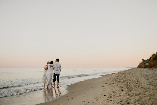 Rückansicht von drei erwachsenen menschen, die sich umarmen, zusammen am strand spazieren gehen