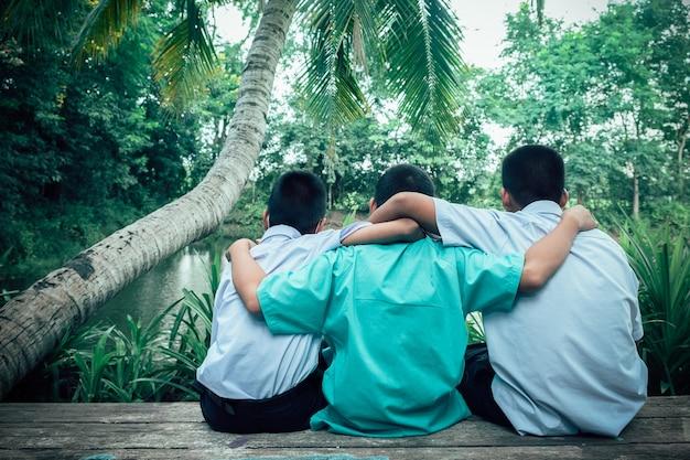 Rückansicht von drei studentenfreunden, die mit liebe umarmen. konzept der besten freundschaft