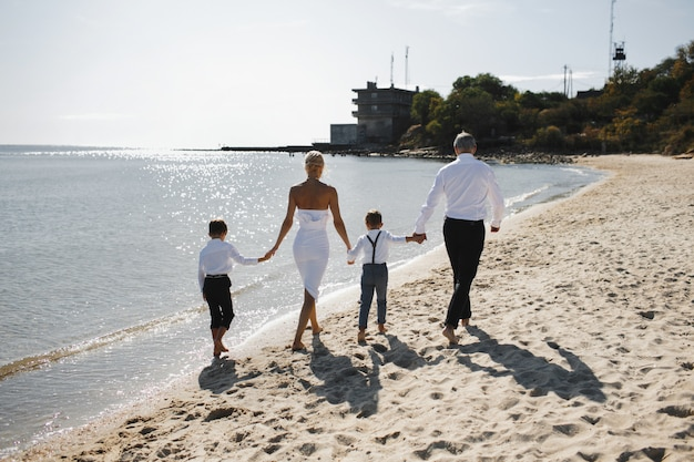 Rückansicht von eltern und kindern halten hände zusammen und gehen am sonnigen sommertag am strand spazieren, gekleidet in weiße stilvolle kleidung