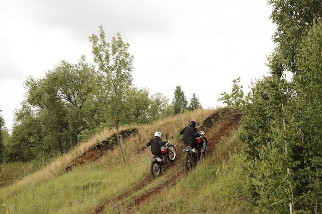 Rückansicht von extremen motorradfahrern in helmen, die geschwindigkeit erreichen, während sie hügel auf unebener straße klettern