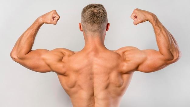 Rückansicht von fit hemdlosem mann, der bizeps zeigt