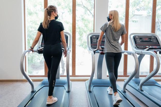 Rückansicht von frauen im fitnessstudio während der pandemie