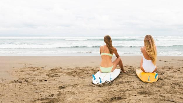 Rückansicht von freundinnen am strand mit surfbrettern
