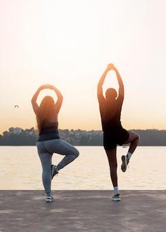 Rückansicht von freundinnen, die yoga bei sonnenuntergang praktizieren