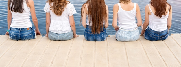 Rückansicht von fünf jungen damen, die jeans und weiße t-shirts tragen
